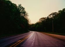 The glowing road moves on. A road draws your eye to the center of the photograph where it promptly takes a turn and disappears into the large and dark trees. it royalty free stock images