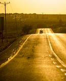 A road at dusk with an aproaching car. A yellow road at dusk with an aproaching car Royalty Free Stock Photo
