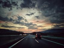 On the road at dusk. Car on a two lanes highway at sunset stock images