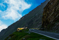 Road on the edge of mountain slope. Asphalt road on the edge of a hillside. dangerous way in mountains Stock Images