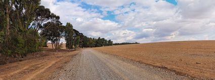 Road at the edge of plowed field and gr Stock Photos