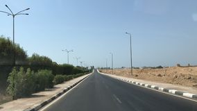 Road between palm trees through the desert. Road in Egypt through the desert against the backdrop of palm trees. Time interval, road with cars, accelerated stock footage