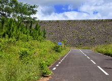 Road on an embankment at a reservoir of fresh water. Mauritius Stock Images