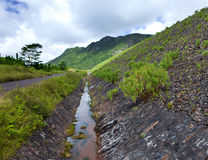 Road on an embankment at a reservoir of fresh water. Mauritius Royalty Free Stock Photography