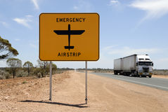 Road with emergency airstrip. Road through the Nullarbor desert in Australia. With road train and sign for an emergency airstrip for the Flying Doctors of Royalty Free Stock Image