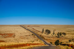 Road through empty grassland Royalty Free Stock Images