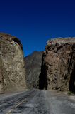 Road entering deep canyon with blue sky. Aspahlt road entering deep canyon with blue sky Royalty Free Stock Photos