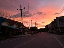 The road enters the village of evening. At the entrance to the village, while the sky orange and pink Stock Images