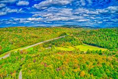 Road through fall foliage from the sky royalty free stock photo