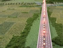 A road through farmland in miniature. Road, farmland, white led lights, and trees in a miniature model city, architecture Stock Image