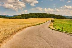 Road through farmlands Stock Photo
