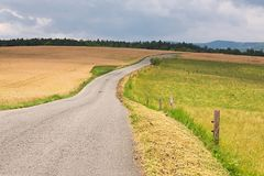 Road through farmlands. Narrow road through agricultural fields Royalty Free Stock Photo