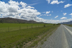 Road and farms' grassland in New Zealand Royalty Free Stock Images