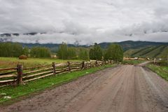 Road, fence and fields. Royalty Free Stock Photography