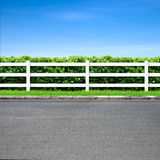 Road and fence. Road side view and white fence on blue sky Royalty Free Stock Photos