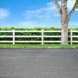 Road and fence. Road side view and white fence on blue sky Royalty Free Stock Photography