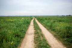 Road field in cloudly summer day Royalty Free Stock Photos