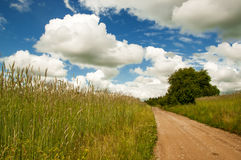 Road in field and cloudy sky Royalty Free Stock Photos
