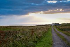 Road through field. Road leading up to a farmhouse across the flat fields on Islay Royalty Free Stock Image