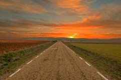Road through the field with orange sky and sunset. Spain Stock Photos
