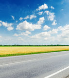 Road, field and sky with clouds Royalty Free Stock Images