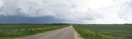Road in the field, stormy sky stock photography