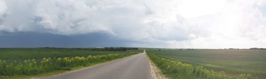 Road in the field, stormy sky royalty free stock images