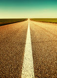 Road through field to horizon Stock Image