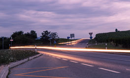 Road between the fields. Road between the corn fieldand car lights at evening. Long exposure photo. State of Vaud, Switzerland Royalty Free Stock Photo