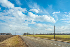 The road among fields in the early spring. Rural road among fields in the early spring on a background of blue sky with clouds royalty free stock photo