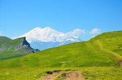 The road through the fields. And views of the Elbrus Stock Photography