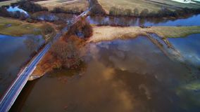 Road through filed tide time, aerial flight view Lithuania stock footage