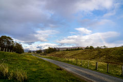 A road through the fileds in Scotland with a vague rainbow. Just after the rain a rainbow is forming Royalty Free Stock Image