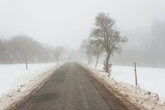 Road in the fog. Mysterious Way. Snowy mountain road. Risk of ice. Royalty Free Stock Photography
