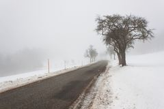 Road in the fog. Mysterious Way. Snowy mountain road. Risk of ice. Royalty Free Stock Images