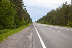 Road in the forest, intercity route. Beautiful green hills. The road that goes beyond the horizon. Road in the forest, intercity route. Beautiful green hills Royalty Free Stock Photo