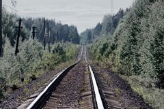 Road through forest. - railway is lost in haze. Summer day, railage. Single-track railroad Royalty Free Stock Photos