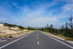 Road in forest with sea. Empty asphalt road with cloudy sky Stock Photos