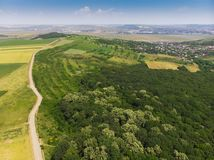 Road in forest to village. Aerial view. Iasi, Romania royalty free stock photography