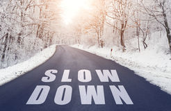 Road in forest in winter with slow down text Royalty Free Stock Photos