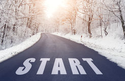 Road in forest in winter with start text Stock Photography
