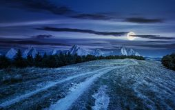 Road through forested mountain ridge at night. In full moon light. beautiful composite landscape with High Tatra mountains in the distance. lovely panorama of Stock Images