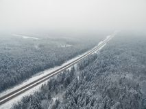 Road in the frozen winter forest with driving cars. Foggy vanishing point perspective. Aerial Royalty Free Stock Image