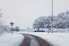 Road with give way signs in the snow Royalty Free Stock Photos