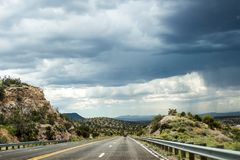 Thunder skyline over rocks and highway. Road going straight ahead, above the road dark thunder sky, around the highway - rocky hills Royalty Free Stock Image