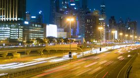 Beautiful night timelapse of a road in Dubai, UAE. On the road going trucks, cars, trains. On both sides of the road are huge skyscrapers Royalty Free Stock Images
