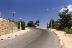 A road going uphill and turning left behind a corner Royalty Free Stock Photo