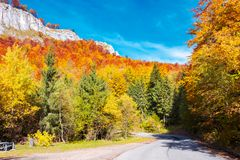 Road through gorgeous serpentine in autumn forest. Huge rocky formation on the hill above the path. beautiful nature and weather. colorful foliage stock image