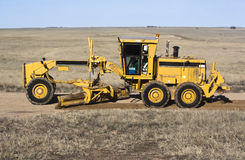 Road Grader. Yellow road grader grading dirt road on prairie Royalty Free Stock Photo