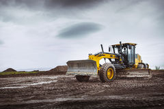 Road grader - heavy earth moving dirty. Road grader - heavy earth moving on dirty ground Royalty Free Stock Images